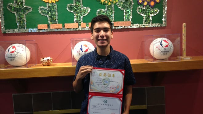 Moorestown Friends student Nick Tursi holds the certificate he received for finishing in the top 30 in a competition in China.