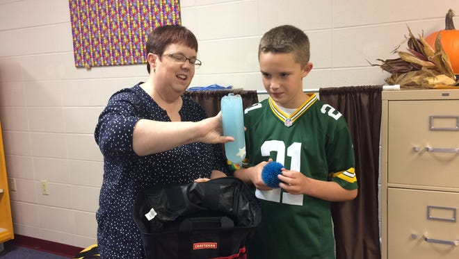 Sturgeon Bay Elementary principal Ann Smejkal explains how to use a glitter timer to David Baxter, who donated several that he made to Sawyer School.