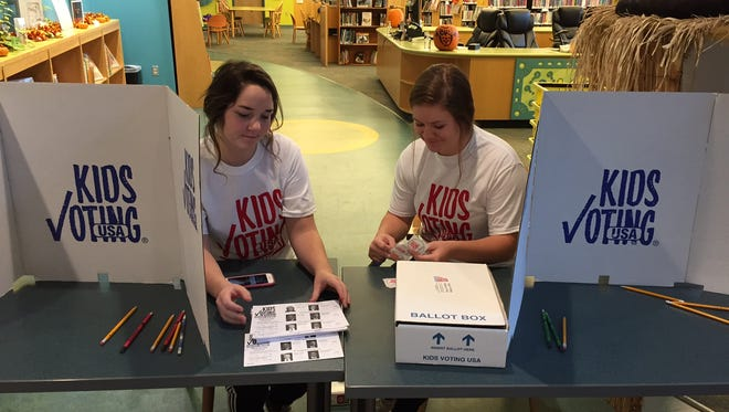 """Independence residents Cassidy Meyer, 15, and Mallory Payton, 15, set up the Kids Voting booth at the Durr Branch of the Kenton County Public Library on Election Day. """"It's important to vote because it is important to exercise your freedom of speech,"""" Payton said."""