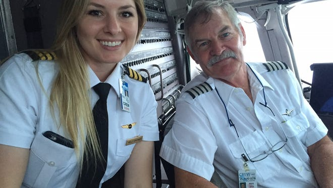 Kelly Brenner, left, and father Paul Brenner shared a cockpit on a recent flight. The younger Brenner is following in her father's footsteps in commercial flight.