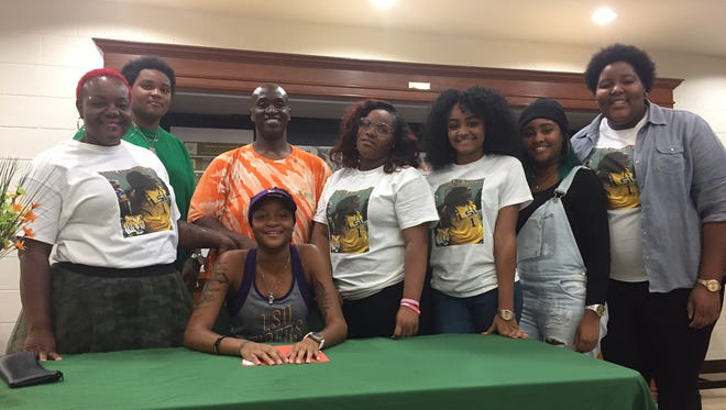 Dunbar senior Dekeriya Patterson, center, signed with LSU on Thursday inside the school's cafeteria.