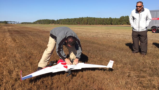 Somerset County Economic Development Commission director Daniel Thompson watches as Jacob Moschler, a data operations analyst in the UAS test program at the University of Maryland checks a 3-pound drone during a drone endurance exercise at the Crisfield airport in Crisfield. Aircraft testing in Crisfield comes before it sets out on an anthropology mission in Central America.