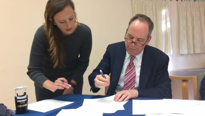 Lawrence University president Mark Burstein, right,signs the conservation easement agreement for Bjorklunden, the university's satellite campus,  in Baileys Harbor Thursday. Also pictured is Jacquie Birkholz a notary from Lawrence University.