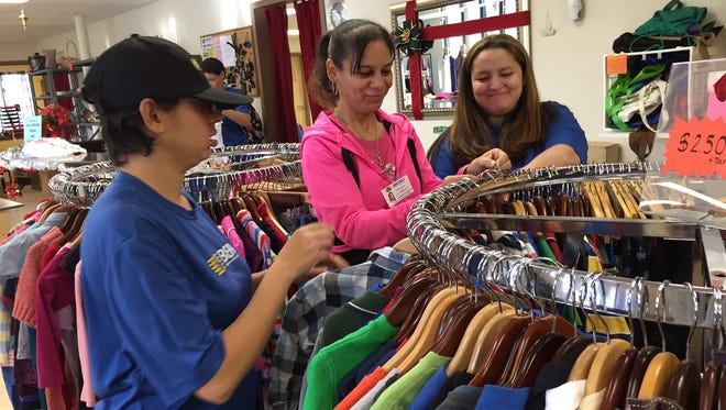 Employees hang clothes at FashionWorks, a combination thrift store and job training program on Clifford Avenue