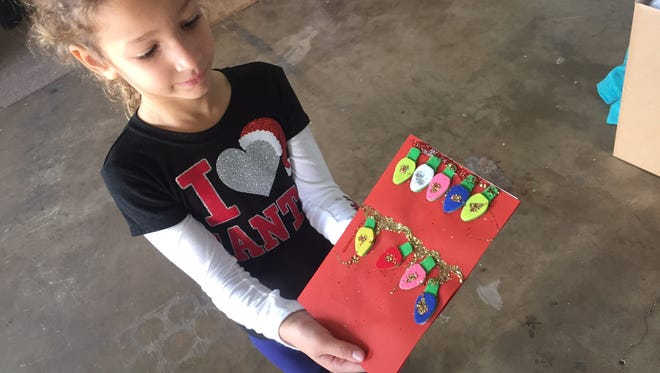 Isabel King holds up one of 1,500 cards made by children at Pineapple Cove Classical Academy, Lockmar Elementary and Mila Elementary. The handmade cards, the brainchild of Isabel's big sister, Madison, 7, will accompany gifts going to Brevard seniors through the Reaching Out Holiday Fund.