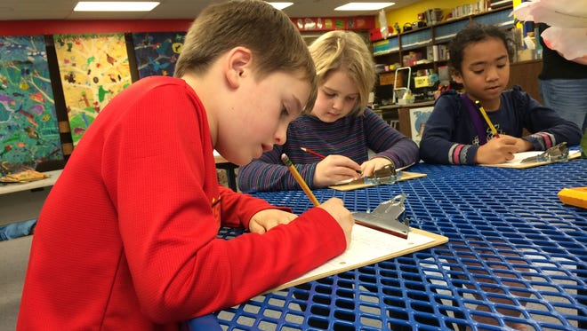 Gibraltar third-grade students Sean Neal, Emma Daubner and Anka Rinkleff work on letters to Santa to help raise money for Make-A-Wish.