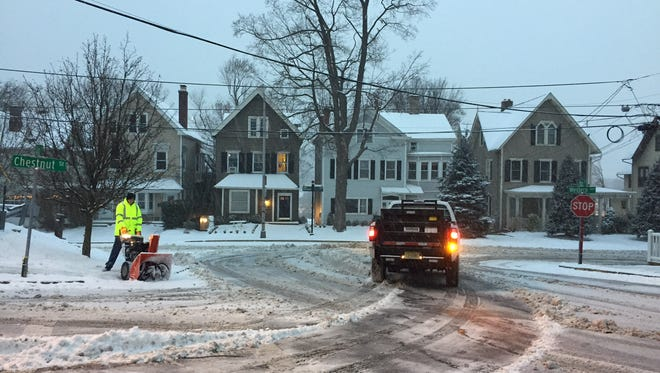 An employee of Morris County's buildings and grounds division clears sidewalk at corner of Western and Chestnut early Saturday, Dec. 17, 2016.