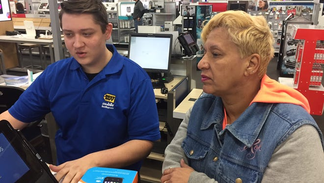At right, Serena Gassendi buys a smart phone for her 9-year-old grandson at Best Buy in Springettsbury Township on Monday. At left, sales associate Jonathan Augustyniak rings up the purchase.