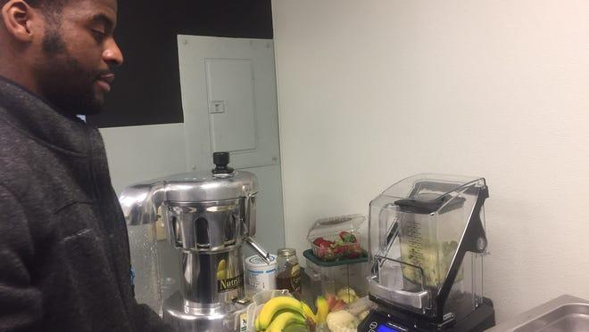 Owner Seth Amoah prepares to make a fresh-pressed juice at The Juice Bar in Merchantville.