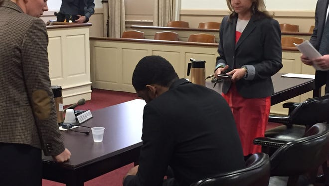 Jamal Nurse, center, bows his head after being found guilty by a Morris County jury of robbing Babies 'R' Us in East Hanover in 2014. He is flanked by defense lawyers Maureen Ingersoll, left, and Elizabeth Martin.