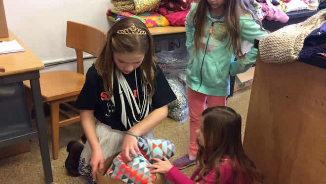 Destination Imagination team member Jordyn Welch (left) helps sisters Shylee (center) and Shaylyn Asher bag items they picked up at the new school store.