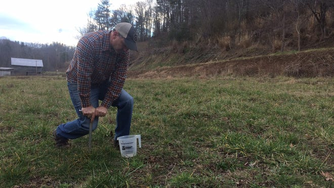 County Extension Director Ross Young drives the soil sample tester into the ground at an East Fork property.