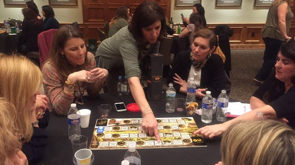 Dena Blizzard explains a prototype of ChardonnayGo! to a group of guests at the Moorestown Community last spring. The game, a spoof on PokemonGo, will be in stores soon.