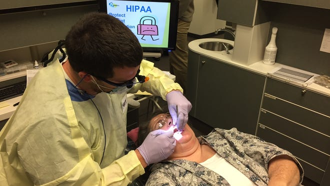 Third-year dental student Matt Lancaster examines Loretta Scarborough in the free dental clinic operated by IU School of Dentistry in space donated by HealthNet at People's Heath Center on the east side.