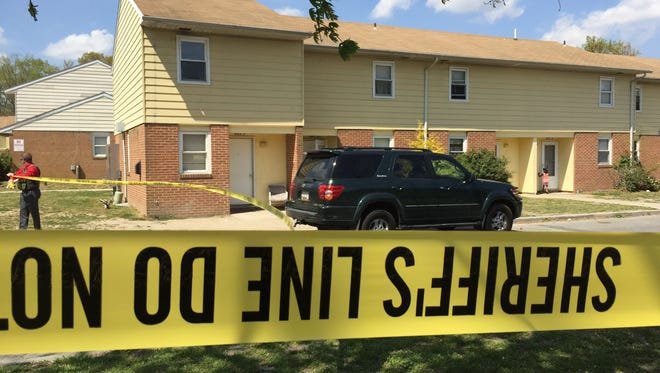 Police tape is wrapped around an area at the Booth Street Apartments where a male victim was shot Friday, April 21, 2017