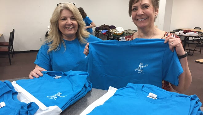 """In this Saturday, April 22, 2017 photo, from left, Lori DeWitt, a professor at Salisbury University and volunteer Janet Boring of West Virginia unpack """"Be The Difference"""" T-shirts for participants in a Craft Connections project that stitches fleece fabric into hat, scarf and mitten combinations for children hospitalized with cancer. DeWitt conceived the Difference Day of community service. Boring learned about the project and traveled the farthest to volunteer."""