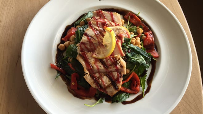 Grilled swordfish  is served with a citrus-pomegranate sauce, chickpeas, kale and roasted tomatoes.