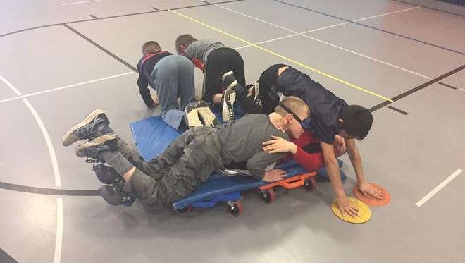 """Students in Stangel Elementary School physical education teacher Jamie Ullman's class participate in the """"Shipwrecked"""" activity, which teaches teamwork and cooperation."""