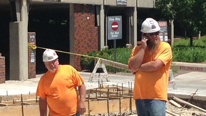 A construction worker places a call at the new driveway on the west side of the Emens Auditorium parking garage.
