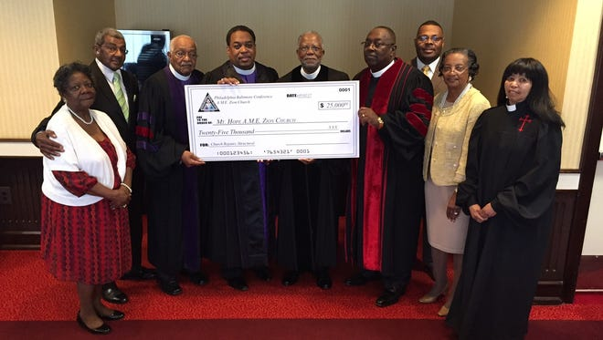 In this June 2017 photo, the Rev. Leon Copeland Sr. (fifth from left), pastor at Mt. Hope AME Zion Church,  joins congregation members in accepting a check for $25,000 from leadership of the African Methodist Episcopal Zion Church. Pictured from left are Cleo Horsey and Allen Handy, Mt. Hope trustees; Bishop Marshall Strickland, retired; Bishop W. Darren More, presiding prelate; the Rev. Leon Copeland, Mt. Hope pastor; the Rev. William Kelly, presiding elder; Jasper Handy, Mt. Hope member; Mary Copeland; and the Rev. Cherry Doane.