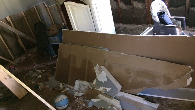The day after the flood, furniture in Moore's living room had been picked up and carried about by flood water, and volunteers had already begun to cut out the ruined drywall.