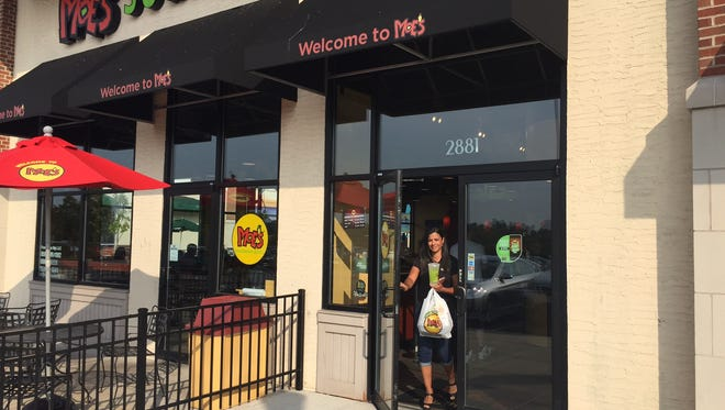 Robyn Bryson walks out of Moe's Southwest Grill in Crestview HIlls to deliver to a Florence customer.