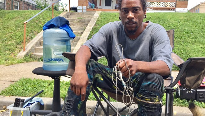 Archie Dale Davis, 33, sits in front of the only house he's ever lived in, on Northern Avenue  in Avondale. His grandfather owns the home, where four generations of the family live.