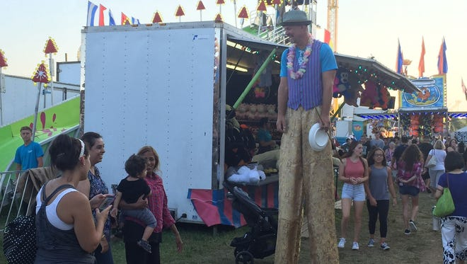 A juggling stilt-walker entertains the crowd at the Middlesex County Fair in East Brunswick.
