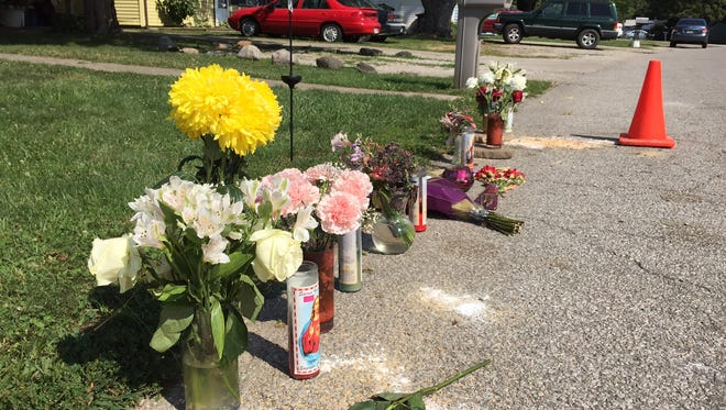 Flowers, candles and other items line the Eastwich Drive Aug. 14, 2017, where two people were killed in a shooting several days prior.