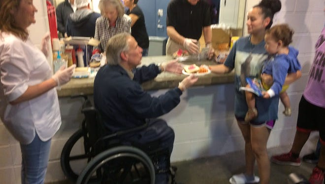 Texas First lady Cecilia Abbott serves dinner with her husband to evacuees of Hurricane Harvey at an Austin shelter.