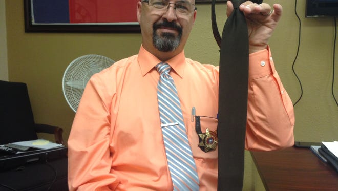 Wichita County Sheriff's Office Chief Deputy Derek Meador holds up a tie Monday that is part of some WCSO personnel uniforms. These ties were rejected for uniform reimbursement by the auditor's office.