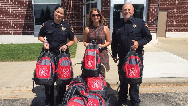 Winnebago County Sheriff John Matz, right, Captain Lara Vendola Messer, left, and Kay-Tee Olds, a member of the REACH-A-Child board and business owner, are pictured with the bags.