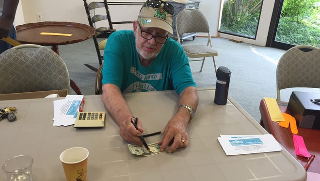 David Mercer uses a counterfeit detection pen on a $20 bill at the Changing Hands Rummage Sale at Unity Church.