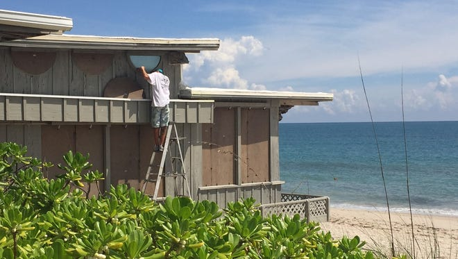 Brett Durfee installs shutters Wednesday, Sept. 6, 2017, on the south end of the Ocean Grill in Vero Beach. The restaurant's bar washed into the Atlantic Ocean during a Thanksgiving storm in 1984. The restaurant otherwise has survived major damage from hurricanes.