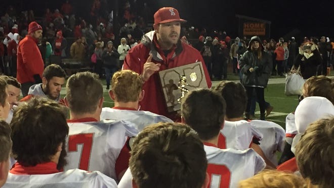 Shelby coach Erik Will, holding the regional championship plaque, huddles with his team after the 42-21 win over Bellevue.
