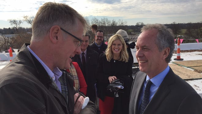 Steve Ricketts with the solar-installation company Solar Energy Solutions, at left, talked with Mayor Greg Fischer atop the Oxmoor Center on in December 2017, amid 2,300 new solar panels.