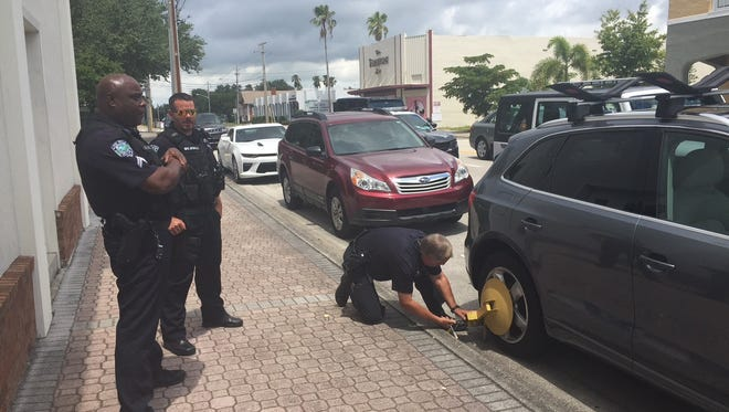 Vero Beach police officers Darrell Rivers and Dan Brumley watch as John Makolin boots a car in downtown Vero Beach June 28, 2017.