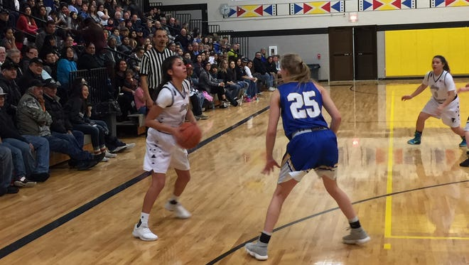 Heart Butte guard Chas'Lin Kipp (left, in white) looks to move the ball during Saturday's home game against Great Falls Central. Bryn Anderson (25 in blue) is defending for the Mustangs.