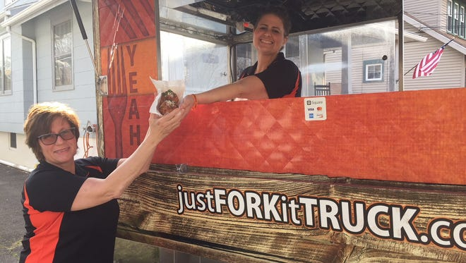 Jillian Daniels hands an 'order' down to her mom, Juliette Daniels, in their Westmont driveway. The mother-daughter team and their Just Fork It food cart will be at many events this season in South Jersey.