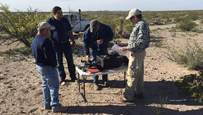 the BLM GIS specialist (center) prepares to fly an unmanned aerial system to gather data for the fire and engineering staff (left and right), who assist with directing the coordinates for this flight.