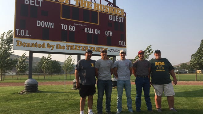 Paul Maki, at far left, and brother Mitch Maki at right, bookend Paul's sons Jaren, Paxton and Holden in front of the new football scoreboard at Remington Field in Belt.