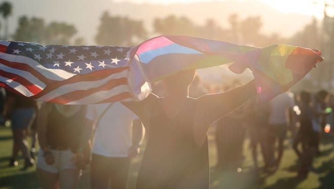 A man carries American and rainbow flags during the 2017 Coachella Valley Music and Arts Festival at Empire Polo Club in Indio. The 2018 festival is scheduled for April 13-15 and April 20-22.
