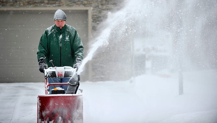 Dick Johnson removes snow from a neighboring driveway
