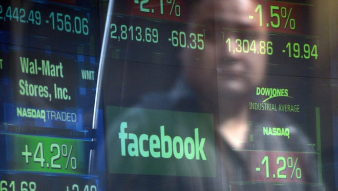 This file photo taken on May 17, 2012 shows a Facebook logo seen through the windows of the NASDAQ stock exchange as people walk by in New York.