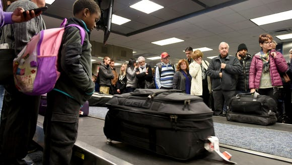 Air Canada passengers stand at Terminal 2 looking for