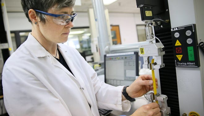 Jamie Brady, a senior lab technician in the Tobey Innovation Center at Brady Corporation. in Glendale, loads a sample of shrink sleeve for wiring into a test machine that will stretch it to failure, so they can judge how it will perform in the field.