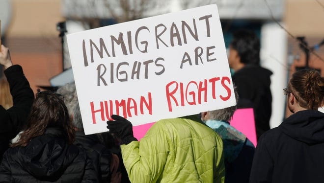 An immigrant-rights supporter holds up a placard during a February rally in Centennial, Colorado.