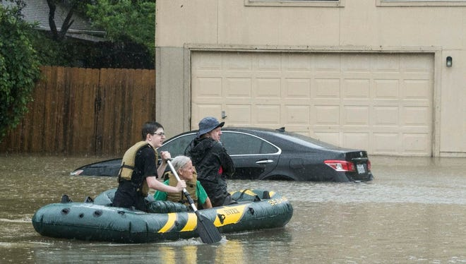 Mary Jackson (center) was rescued by local residents in west Houston after being stranded by floodwater.
