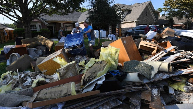 Members of the Olson family remove debris and damaged items Aug. 31, 2017, from their father's home in the Twin Oaks Estate after Hurricane Harvey caused widespread flooding in Houston, Texas.
