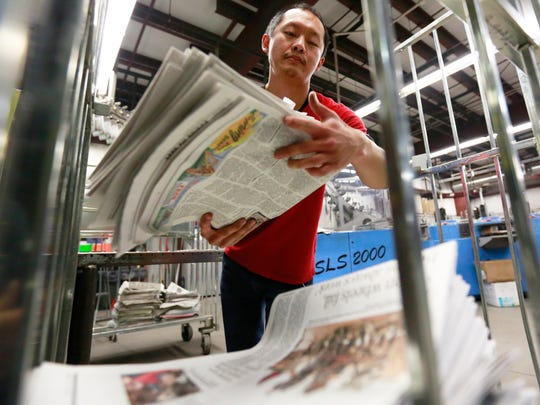 Xue Xiong of Wausau stacks Monday's newspapers for delivery at the Wausau Daily Herald printing press in Wausau, Wisconsin.